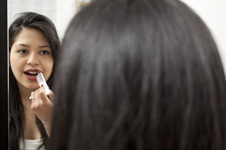 Portrait of beautiful woman applying lipstick close up in the mirror photo