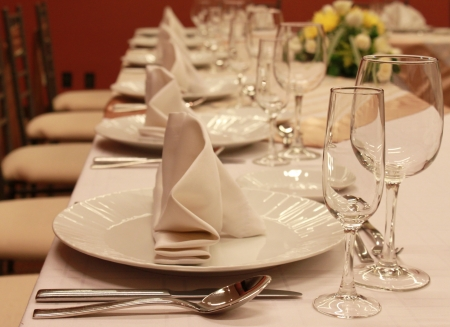 Glasses and plates on table in restaurant background photo