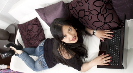 Full length of a young lady sitting on sofa, working on laptop Stock Photo - 14454502
