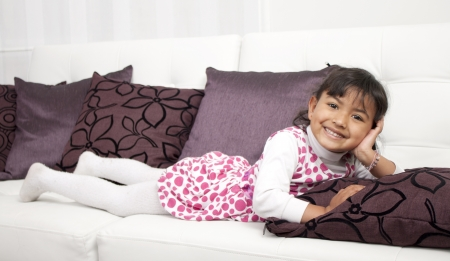 Happy thoughtful girl lying on sofa  Stock Photo - 17382438