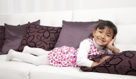 Happy thoughtful girl lying on sofa Stock Photo - 17382438