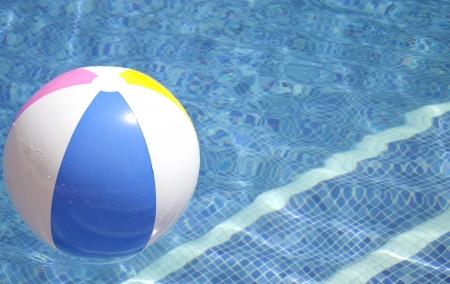 bola de billar: Una pelota de colores flotando en una piscina azul Foto de archivo