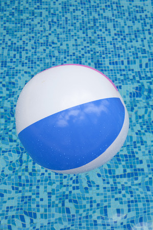 A colorful ball floating in a blue swimming pool photo