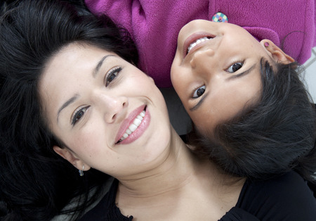 Child and her mum portrait on the floor where both are smiling Stock Photo - 27721754