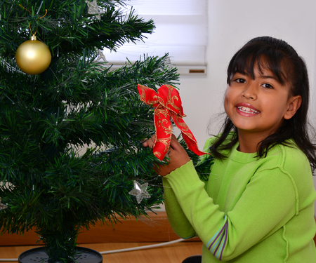 latin family: Child decorating a Christmas tree with baubles