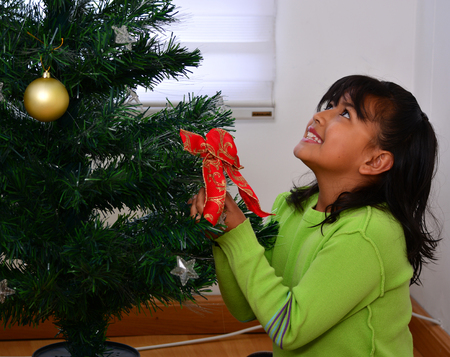 decorating christmas tree: Children decorating a Christmas tree with baubles in the living-room Stock Photo