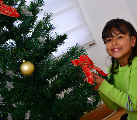 decorating christmas tree: Daugther decorating a Christmas tree with baubles in the living-room