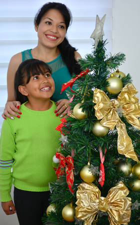 latin family: Young family decorating a Christmas tree