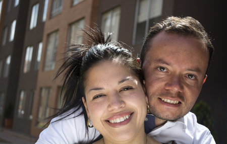 Attractive, very happy young couple embracing and smiling in front of their new first home.