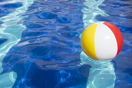 Beach ball floating in swimming pool abstract concept for summer vacations.