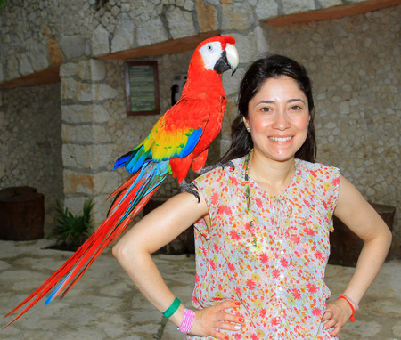 Portrait of a young woman with her domestic ara parrot.