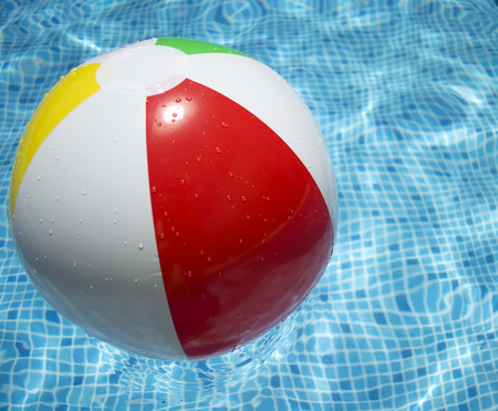 Colorful ball floating in a blue swimming pool. Stock Photo