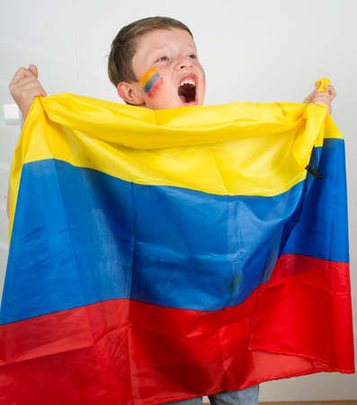 Happy young boy holding an Colombian flag.