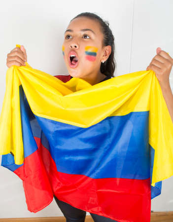 Happy young girl holding an Colombian flag.