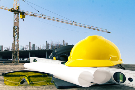 civil engineer: file of safety helmet and architect plant on wood table