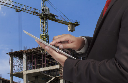 indenture: Businessman on background of new highrise apartment buildings and construction cranes on background