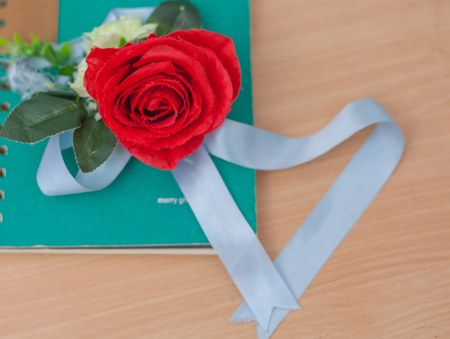 Red roses and notebook on wood background, love concept Stock Photo