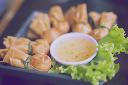 Toong thong,Thai food, oriental deep fried wontons filled with prawn and spring onion, served with dumpling and sauces,vintage color