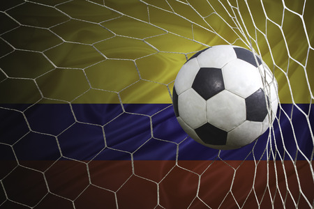 Colombia flag and soccer ball, football in goal net Stock Photo