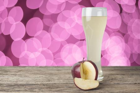 vaso de precipitado: jugo de manzana sobre la mesa de madera, fondo bokeh