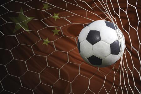 China flag and soccer ball, football in goal net Standard-Bild