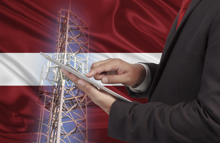 hands free device: business and mobility communications concept Latvia Flag background Stock Photo