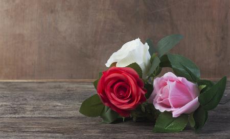 Three roses:red, white, pink lie on a wooden Standard-Bild