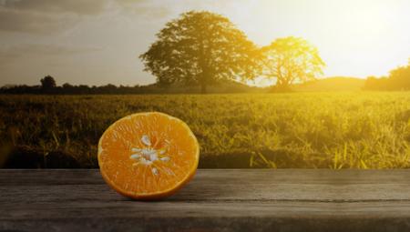 Orange, half of orange, orange  on the wooden table on the sunset blurred background