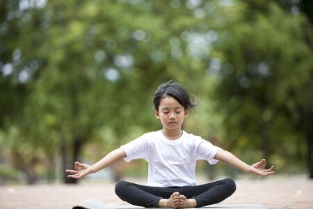 beautiful Asian children meditating in lotus position