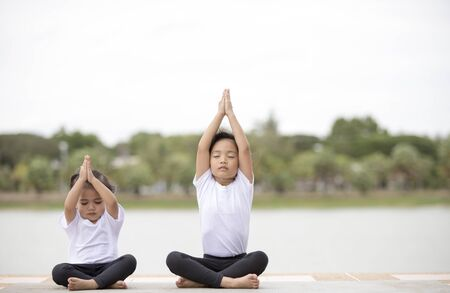 beautiful little asian child girl doing yoga in the public park.
