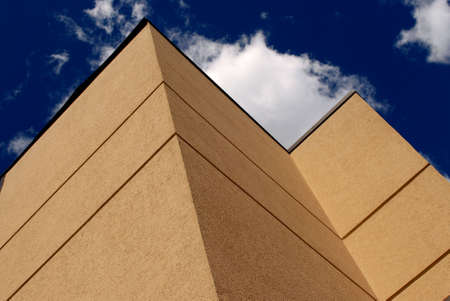 Photo of corner of building showing blue sky and clouds. Stock Photo
