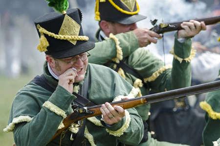 rifleman: Fort Erie, Ontario, Canad� - agosto 62011- Un soldado estadounidense reenactor del Regimiento 1 de bits de fusilero del papel de su pr�xima ronda mientras carga su arma en el cerco anual de fin de semana Fort Erie, una recreaci�n de uno de los principales batallas de la W Editorial