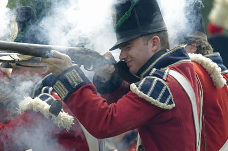 erie: FORT ERIE, ONTARIO, CANADA - August 62011- A British soldier fires his weapon at the American Infantry at the annual Siege of Fort Erie weekend , a reenactment of one of the major battles of the War of 1812.
