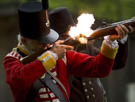 reenactor: Una guerra de 1812 reenactor dispara su fusil en una exhibici�n en el Museo de Jordania Editorial