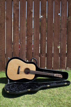 Guitar in case in front of a tall redwood fence. photo