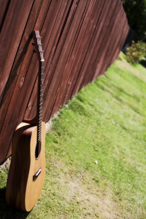 Vibrant guitar leaning against a redwood fence. photo