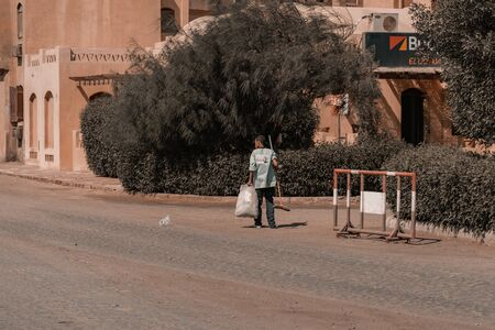 A Man from behind worker collect waste in the middle of a city downtown in Egypt, El Gouna. North Africa. Imagens - 131853666