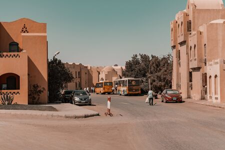 A Man from behind worker collect waste in the middle of a city downtown in Egypt, El Gouna. North Africa.