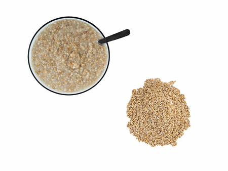 Top view of cooked steel cut oats in bowl next to pile of raw steel cut oats on white background