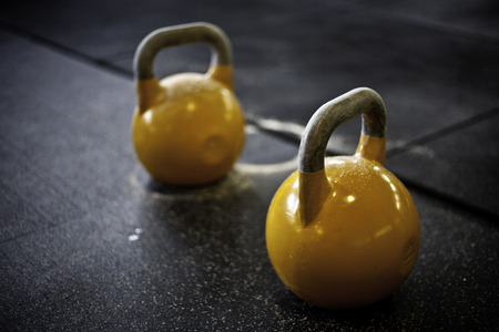 two yellow kettlebells in a crossfit gym
