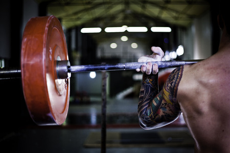 Tattooed man practicing weightlifting in a gym crossfit
