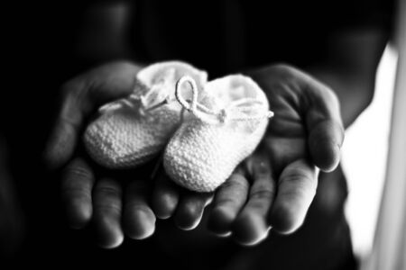 baby's bootees in the hands of his father