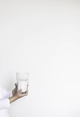 Hands of a child holding a glass of milk isolated on white background Stock Photo