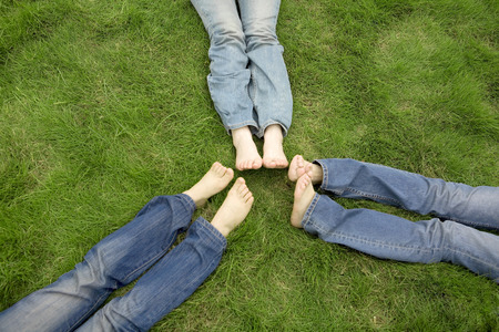 non moving activity: Three girls lying on lawn with foot by foot Stock Photo