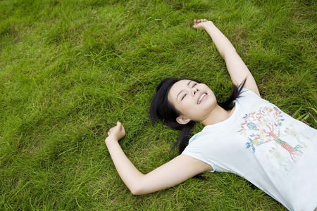 raised viewpoint: Girl lying on lawn Stock Photo