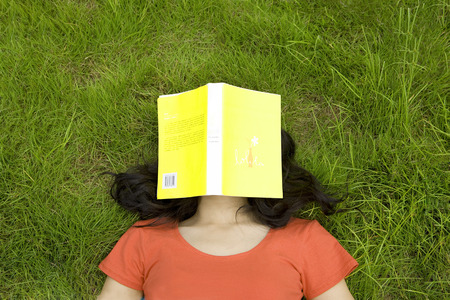 medium length: Girl lying on lawn with book covering face Stock Photo