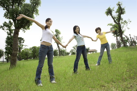 raised viewpoint: Three girls lying on lawn with hand in hand Stock Photo