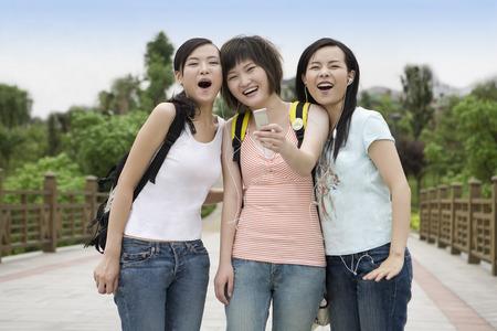 non moving activity: Three girls listening music on the stone bridge