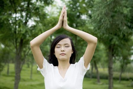 desires 25: Girl on the lawn raising hands praying Stock Photo