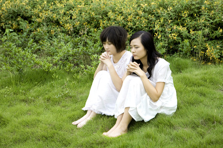 non moving activity: Two girls sitting on lawn praying